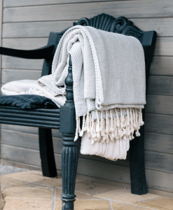 Two Fairtrade organic cotton hemmingway throws on a chair outside