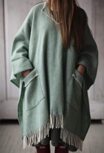 An ethically sourced green Fairtrade cotton blanket that can be worn as a poncho